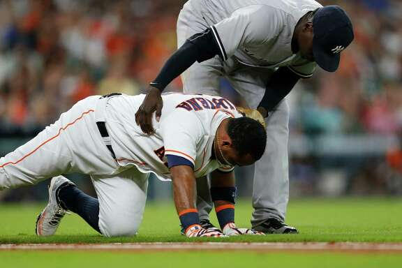 New York Yankees shortstop Didi Gregorius (18) checks on Houston Astros third baseman Luis Valbuena (18) after he fell running up the first base line on a grounder during the second inning of an MLB game at Minute Maid Park, Tuesday, July 26, 2016, in Houston.