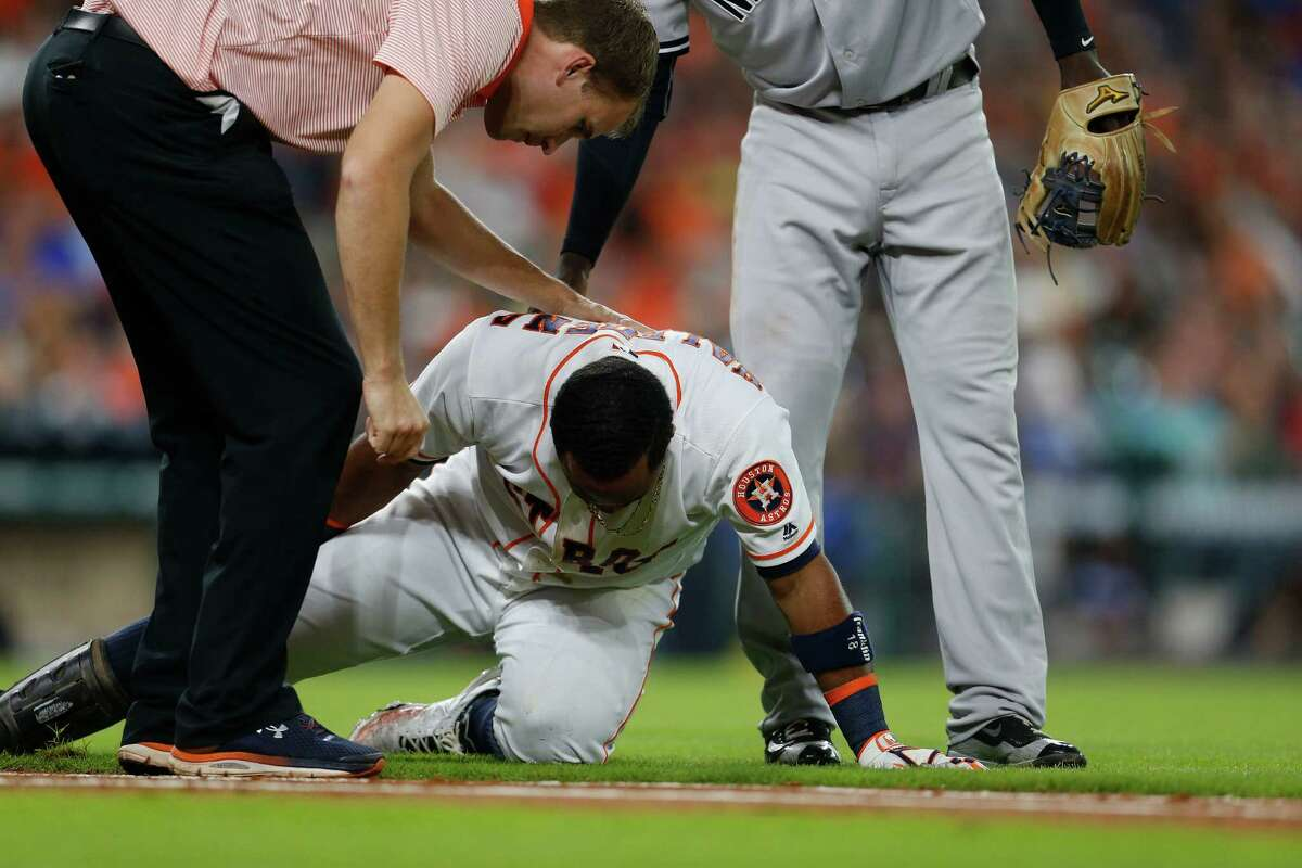 Houston Astros trainer Jeremiah Randall, and New York Yankees shortstop Didi Gregorius (18) checks on Luis Valbuena (18) after he fell running up the first base line on a grounder during the second inning of an MLB game at Minute Maid Park, Tuesday, July 26, 2016, in Houston.