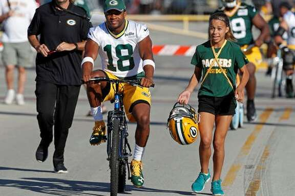 In a time-honored tradition at the Packers' training camp, wide receiver Randall Cobb gets some assistance from a fan while biking to the practice field.