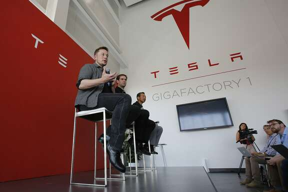 Elon Musk, CEO of Tesla Motors Inc., left, discusses the company's new Gigafactory Tuesday, July 26, 2016, in Sparks, Nev. It's Tesla Motors biggest bet yet: a massive, $5 billion factory in the Nevada desert that could almost double the world's production of lithium-ion batteries by 2018. In the center is J.B. Straubel, Tesla's chief technical officer and at right is Yoshihiko Yamada, executive vice president of Panasonic. (AP Photo/Rich Pedroncelli)