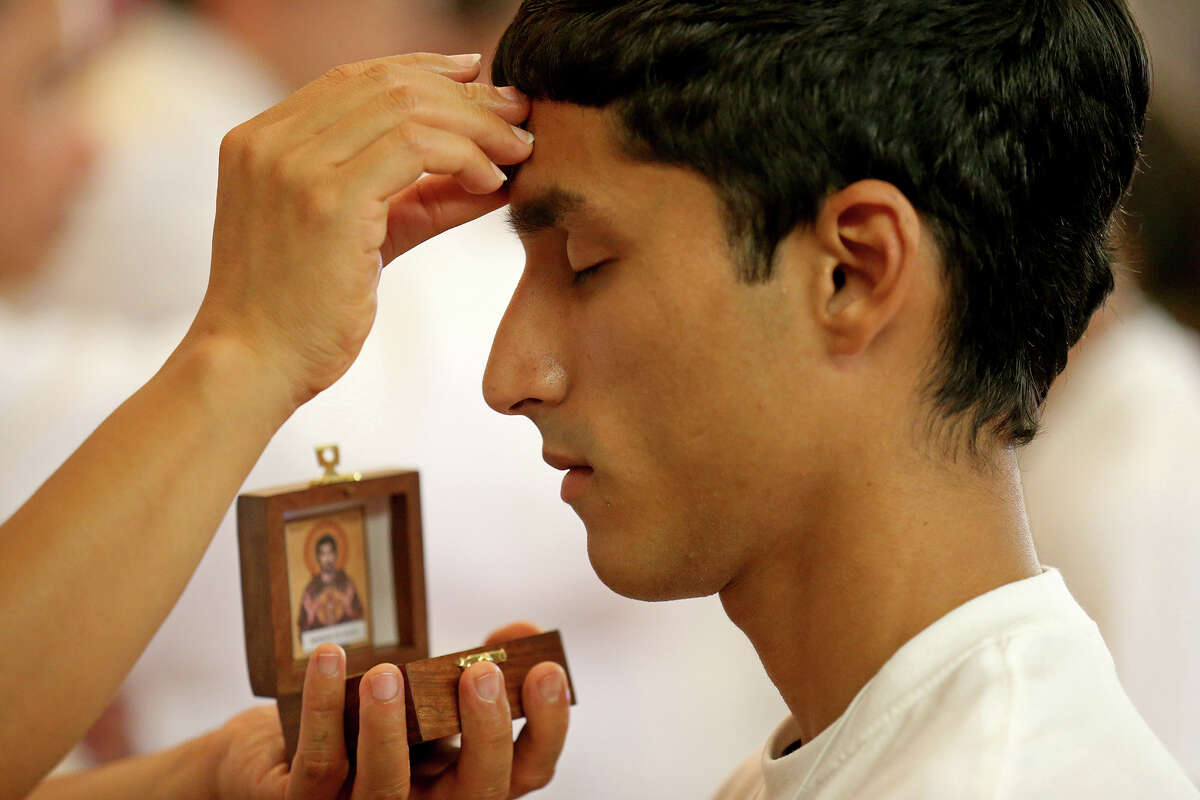 Eduardo Garza, 17 of Roma, Tx. is blessed with a Saint Francis of Assisi relic by Giovanni Ada, director of the office of youth ministry of the diocese of Brownsville, during the World Youth Encounter Day part of the celebration of World Youth Day held at Saint Anne Catholic Church in the Pueblo de Palmas colonia in Penitas, Tx.