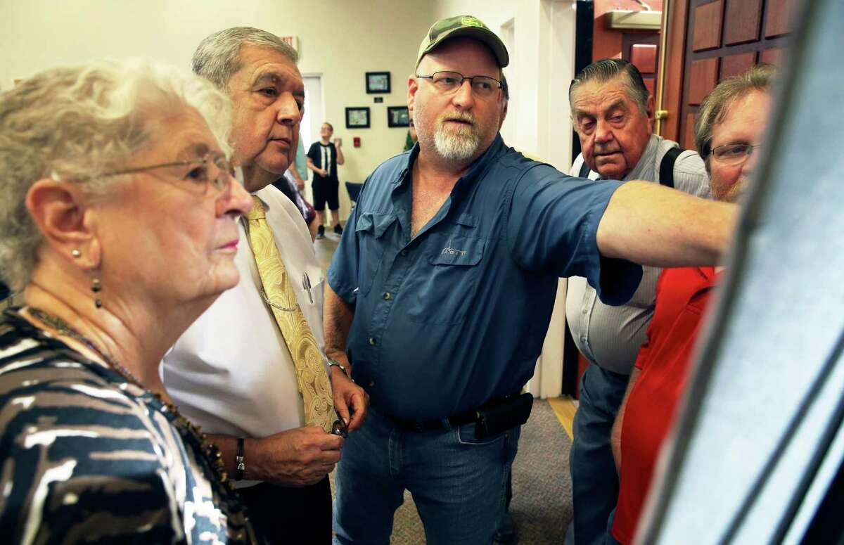 Property owner Matt Beck points out where his land intersects the proposed toll road to Cibolo City Manager Robert Herrera (center left) as the Cibolo City Council prepares to hold to a public meeting on July 26. The council is considering a seven-mile toll road from the city to Interstate 10. Watching on left is Dorothy Nell. Looking over Beck's shoulder is land owner Robert Lee Schulze.
