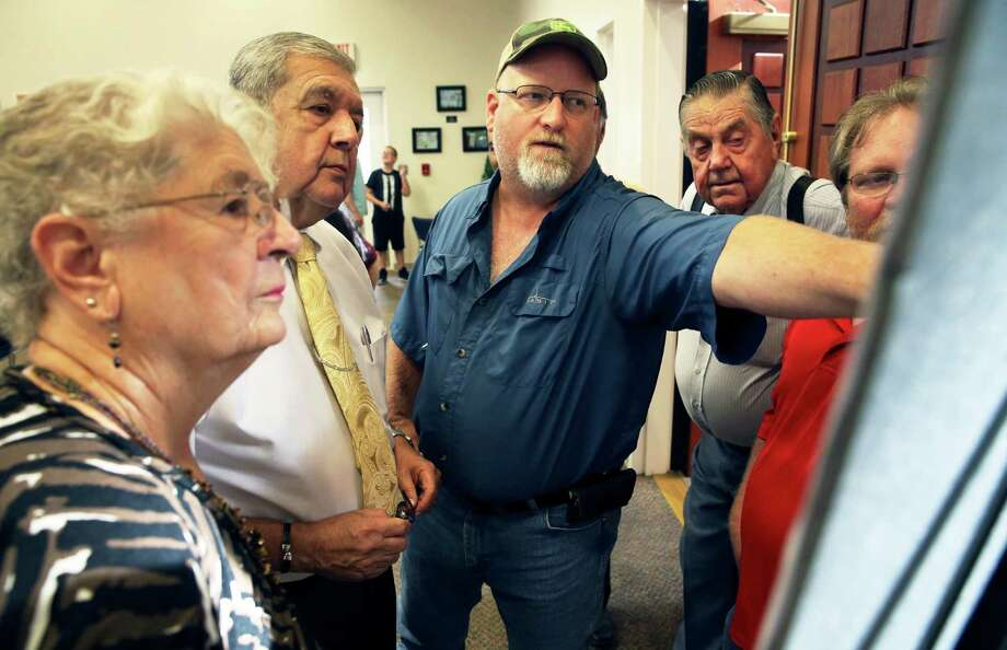Property owner Matt Beck points out where his land intersects the proposed toll road to Cibolo City Manager Robert Herrera (center left) as the Cibolo City Council prepares to hold to a public meeting on July 26. The council is considering a seven-mile toll road from the city to Interstate 10. Watching on left is Dorothy Nell. Looking over Beck's shoulder is land owner Robert Lee Schulze. Photo: Tom Reel /San Antonio Express-News / 2016 SAN ANTONIO EXPRESS-NEWS