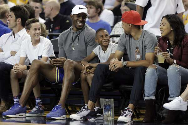 Andre Iguodala (white hat) laughs with Stephen Curry (red hat) as they watch the game with their families during the first half as the USA Mens National basketball team played the China Mens National team at Oracle Arena in an exhibition game in Oakland , Calif., on Tuesday, July 26, 2016. The teams head to Rio for the Olympics beginning on August 6.
