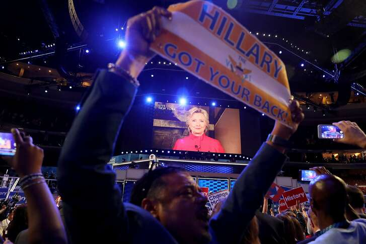 PHILADELPHIA, PA - JULY 26:  Delegates cheer as a screen displays Democratic presidential candidate Hillary Clinton delivering remarks to the crowd during the evening session on the second day of the Democratic National Convention at the Wells Fargo Center, July 26, 2016 in Philadelphia, Pennsylvania. Democratic presidential candidate Hillary Clinton received the number of votes needed to secure the party's nomination. An estimated 50,000 people are expected in Philadelphia, including hundreds of protesters and members of the media. The four-day Democratic National Convention kicked off July 25.  (Photo by Joe Raedle/Getty Images)