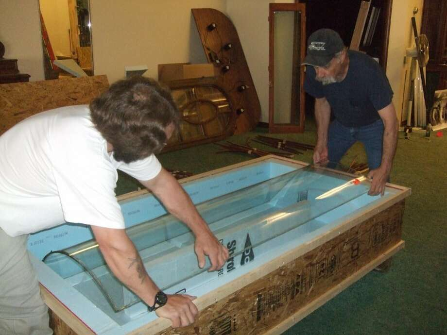 Hayley Cox/Plainview Daily Herald CRATING: Richard Tenore (left), a carpenter from Connecticut, and Jerry Albright of Plainview carefully place a curved section of the Passport Gifts storefront in a crate designed to protect the antique glass for shipping to Connecticut where it will be reassembled.