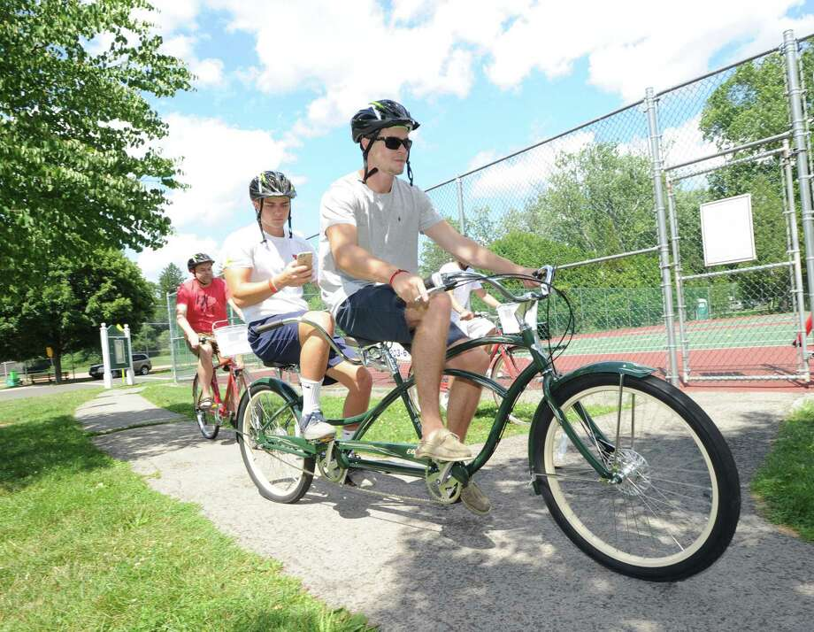 Scott Atkinson, left, and Matt Motill, use a two-seated bicycle as the pair participated in the Arch Street Teen Center Pokemon Go bike tour in Bruce Park, Greenwich, Conn., Tuesday, July 19, 2016. The bicycke is one of 18 new bicycles purchased with a grant that will be used by the teen center for summer riding tours on Tuesdays and Thursdays said Kyle Silver, riding at rear, the executive director of the teen center who was leading the bike tour. Photo: Bob Luckey Jr. / Hearst Connecticut Media / Greenwich Time
