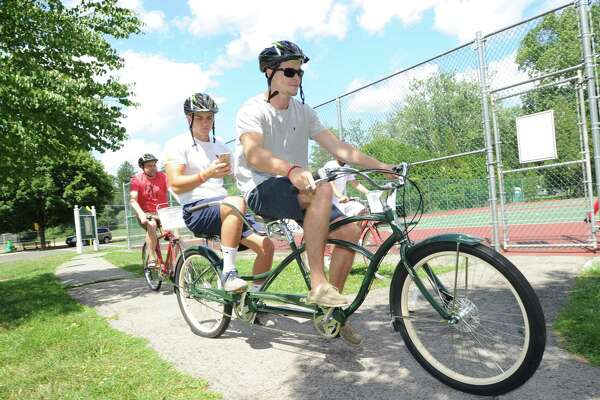 Scott Atkinson, left, and Matt Motill, use a two-seated bicycle as the pair participated in the Arch Street Teen Center Pokemon Go bike tour in Bruce Park, Greenwich, Conn., Tuesday, July 19, 2016. The bicycke is one of 18 new bicycles purchased with a grant that will be used by the teen center for summer riding tours on Tuesdays and Thursdays said Kyle Silver, riding at rear, the executive director of the teen center who was leading the bike tour.