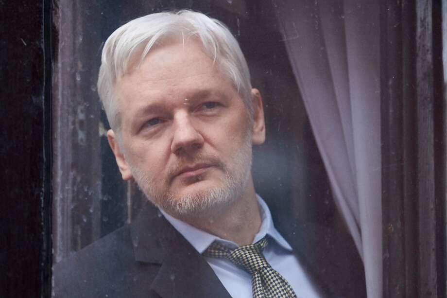 This file photo taken on February 05, 2016 shows WikiLeaks founder Julian Assange looking out of the balcony window of the Ecuadorian embassy in central London on February 5, 2016 before addressing the media from the balcony. WikiLeaks founder Julian Assange started his fifth year camped out in the Ecuadoran embassy in London on June 19, 2016, an occasion his supporters were to mark with events celebrating whistleblowers. Photo: NIKLAS HALLE'N, AFP/Getty Images