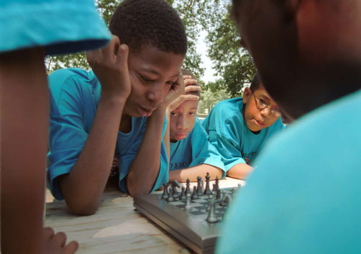 Stamford_071202-Jefferson Elie [center] gets help with his chess game against Kenneth King[back to camera] from Chad Pennix and Ryan Burke. They're attending the YMCA teen camp and come to Scalzi Park every Friday. Dru Nadler/photo