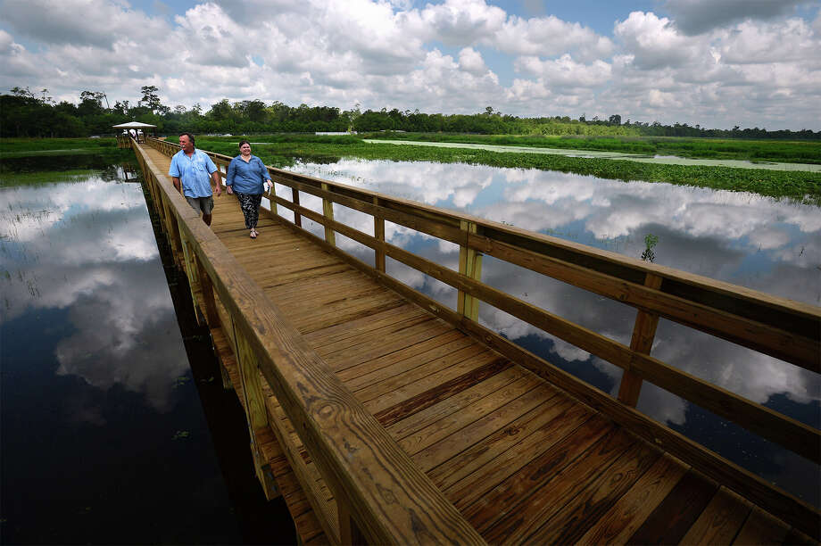 Doug Oldbury and Elizabeth Eddins walk Tuesday across the newly opened boardwalk at Cattail Marsh in Beaumont. The more than 500 foot span allows guests to walk over the wetlands for a closer look into the manmade marshlands.  Photo taken Tuesday, July 26, 2016 Guiseppe Barranco/The Enterprise Photo: Guiseppe Barranco, Photo Editor
