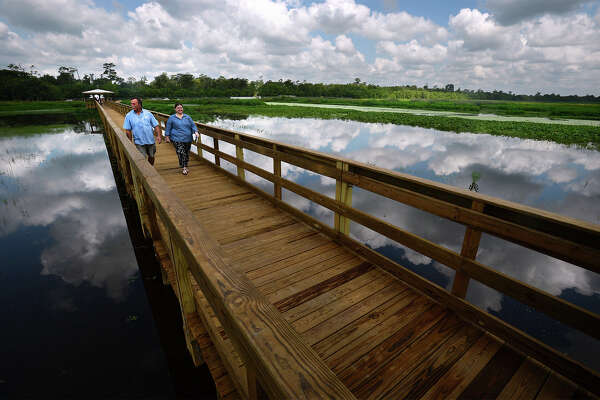Doug Oldbury and Elizabeth Eddins walk Tuesday across the newly opened boardwalk at Cattail Marsh in Beaumont. The more than 500 foot span allows guests to walk over the wetlands for a closer look into the manmade marshlands.  Photo taken Tuesday, July 26, 2016 Guiseppe Barranco/The Enterprise