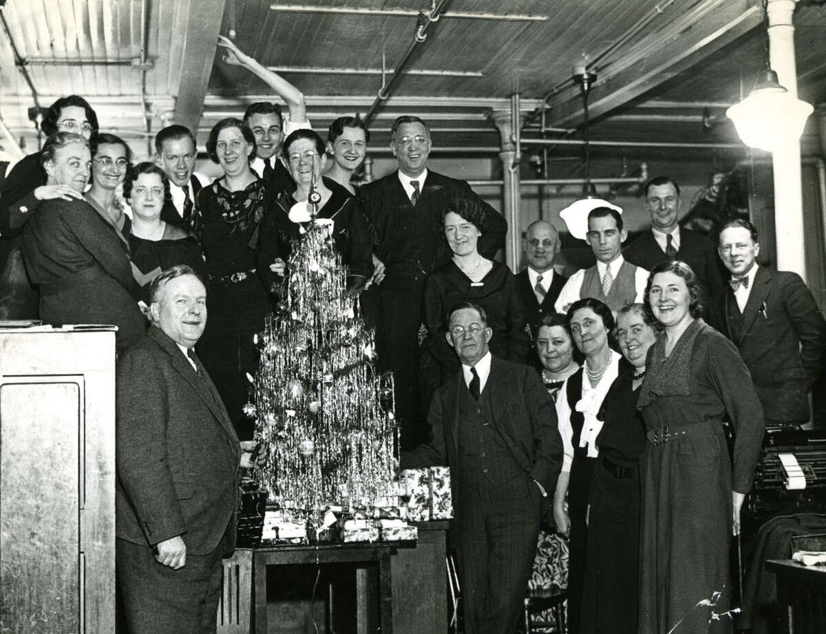 Albany Evening News business office staffers celebrate during a Christmas party Jan. 31, 1934. Publisher is pictured at right of tree. Historic (Times Union archive)
