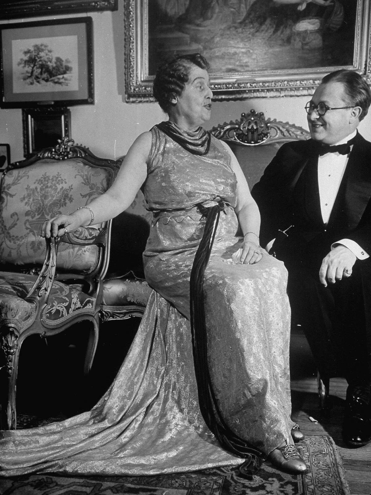 American socialite and amateur soprano vocalist Florence Foster Jenkins (1868 - 1944) talks with an unidentified guest at a formal event in her home, 1937. Foster was known (and loved) primarily for her almost complete lack of vocal skill.