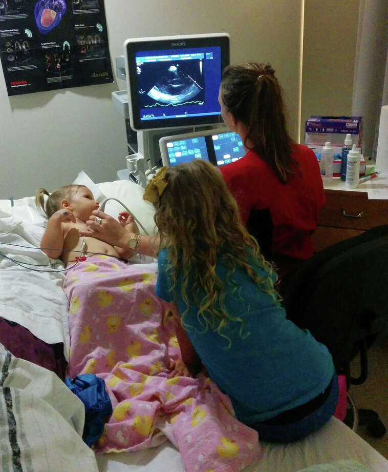 An Alvin Community College diagnostic cardiovascular sonography student performs a heart scan on a young volunteer.