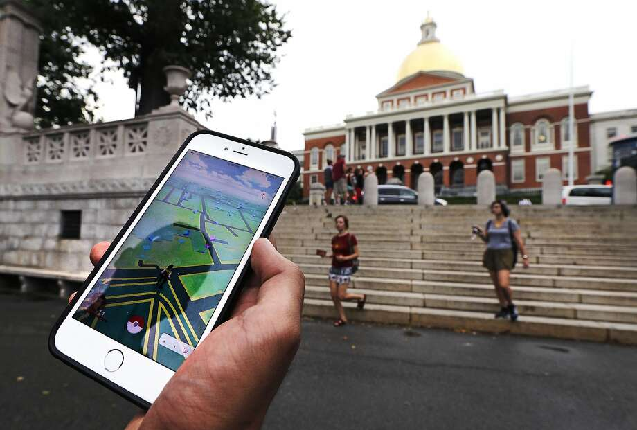 "In this Monday, July 18, 2016, photo, a ""Pokemon Go"" player shows his mobile phone while walking through the Boston Common, outside the Massachusetts Statehouse in Boston. Historical markers dot the landscape of old cities, barely noticed by passers-by. The founder of the volunteer-based historical markers website that licensed its data to game-maker Niantic Labs five years ago said he hopes enough people take their eyes off the Pokemon they're trying to catch to read the history on the markers. On the opposite side of the wall, left, is a bronze memorial to Robert Gould Shaw and the 54th Regiment Massachusetts Volunteer Infantry, comprised of black Union soldiers who fought in the Civil War. (AP Photo/Charles Krupa) Photo: Charles Krupa, Associated Press"