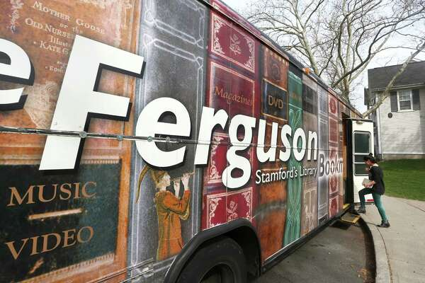 Ferguson Library employee Ashley Hamel boards the Ferguson Library Bookmobile during a stop at the Chester Addison Community Center on Thursday, March 31, 2016.