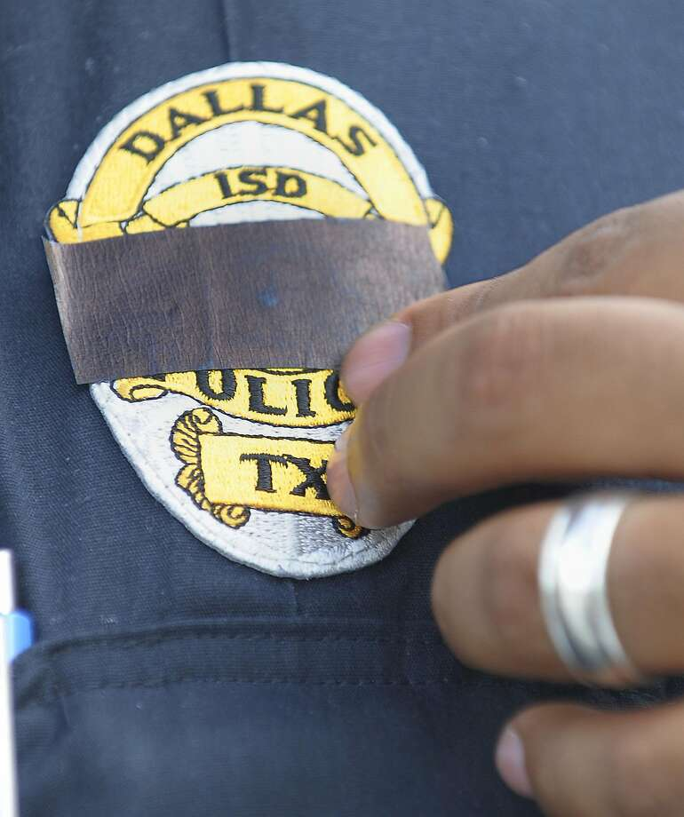 A Dallas independent school district police officer adjusts black tape over his badge to honor the five officers killed in an ambush by a gunman on July 8. Photo: Max Faulkner, TNS