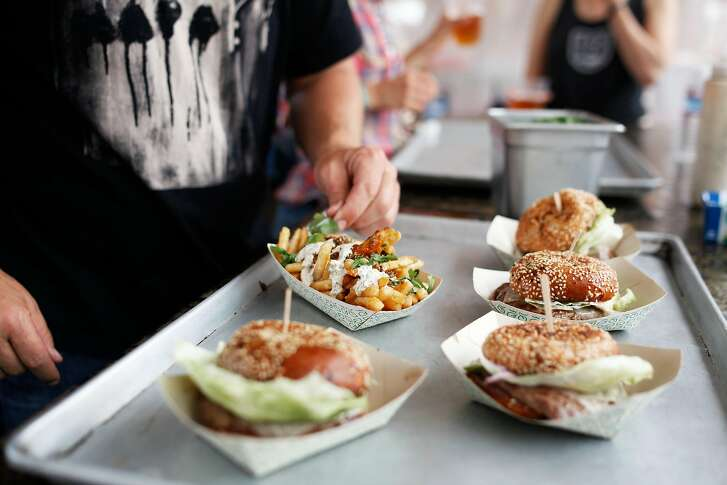 """Garlic Chimichurri Fries and Best Damn Cheeseburgers are prepared at the """"4505 Burgers and BBQ"""" stand at Outside Lands on Sunday, Aug. 10, 2015."""