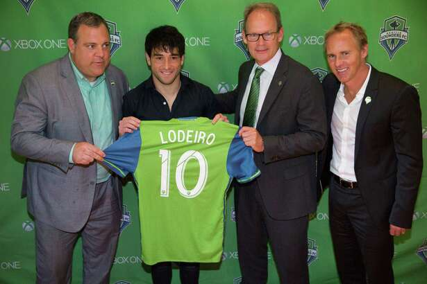 Nicolas Lodeiro poses for photos with Sounders GM Garth Lagerwey, interim head coach, Brian Schmetzer, and sporting director Chris Henderson following press conference welcoming Lodeiro as a midfielder to the Seattle Sounders, at The Ninety on Wednesday, July 27, 2016.