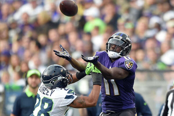 Seattle Seahawks defensive back Marcus Burley (28) breaks up a pass intended for Baltimore Ravens wide receiver Kamar Aiken (11) during the second half an NFL football game, Sunday, Dec. 13, 2015, in Baltimore. (AP Photo/Nick Wass)