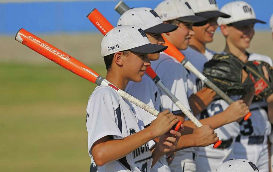 Gabe Herrera (front) along with other members of the McAllister Park Little League 11-12 year-old squad pose for pictures in part to celebrate their state championships in three age divisions of little league baseball on July 28, 2015. Photo: Kin Man Hui /San Antonio Express-News / ©2015 San Antonio Express-News