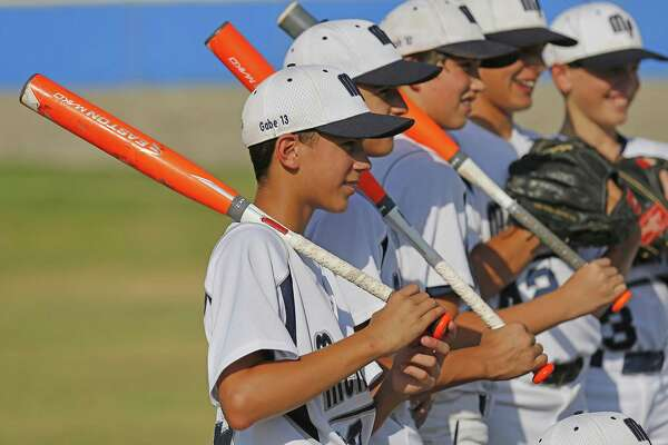 Gabe Herrera (front) along with other members of the McAllister Park Little League 11-12 year-old squad pose for pictures in part to celebrate their state championships in three age divisions of little league baseball on July 28, 2015.