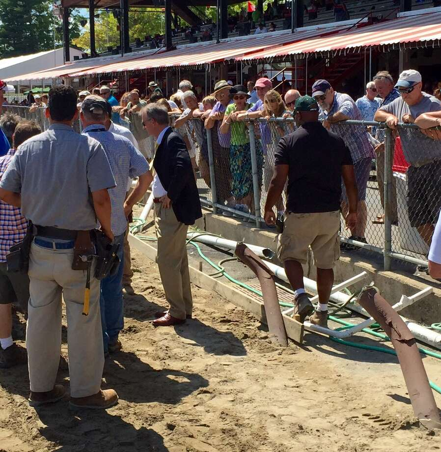 Workers survey the damange after the starting gate crashed into the rail Wednesday at Saratoga Race Course. (Skip Dickstein / Times Union)