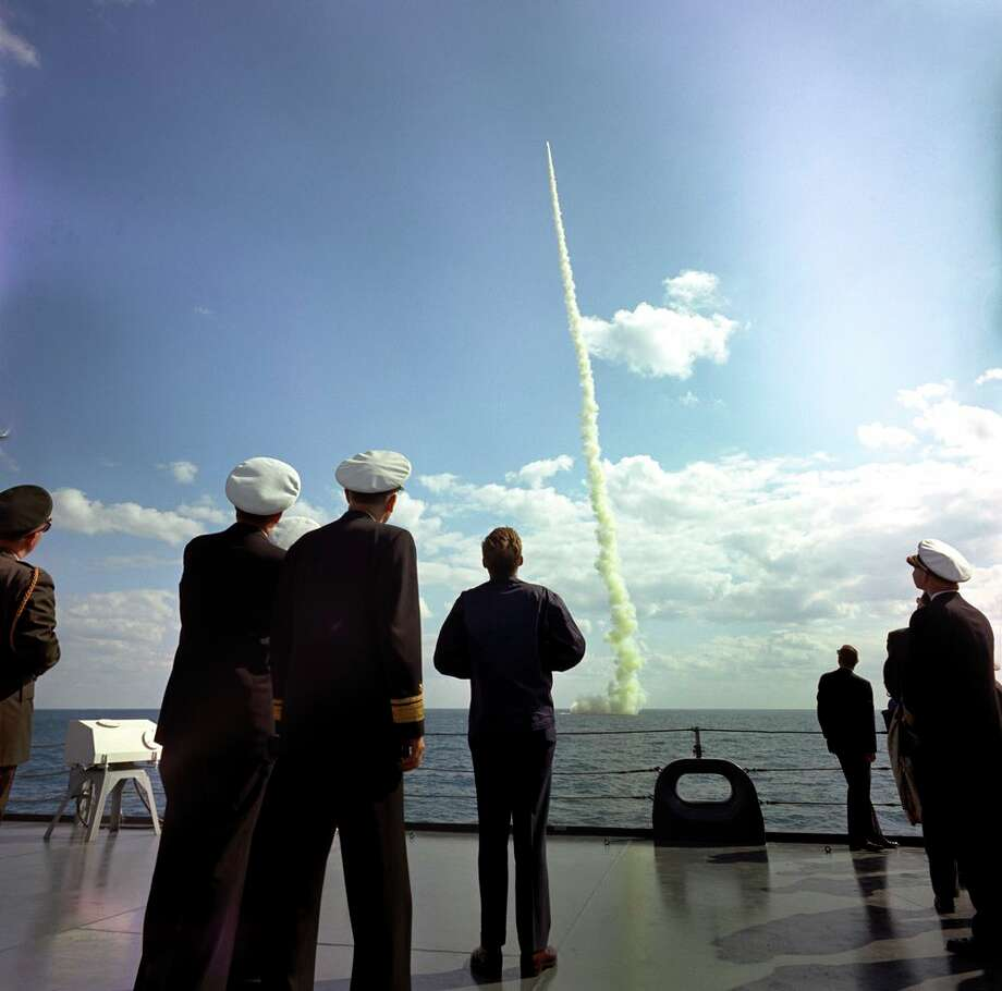 During a visit aboard the United States Naval ship USS Observation Island (EAG-154), President John F. Kennedy (center) watches a demonstration of the firing of a Polaris A-2 missile from the submarine USS Andrew Jackson (SSBN-619), at sea off the coast of Florida. Photo: Robert Knudsen. White House Photographs. John F. Kennedy Presidential Library And Museum, Boston