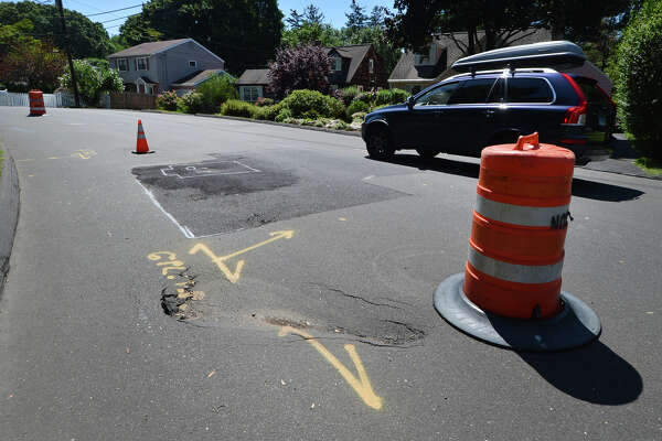 Highway cones and barrels divert traffic into one lane on a curve around a sinkhole on Lockwood Lane in Norwalk.