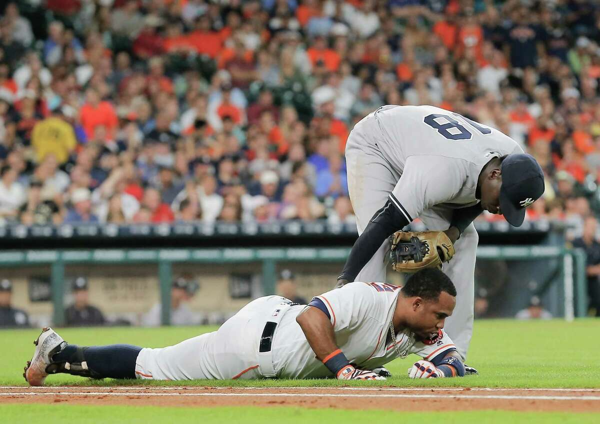 HOUSTON, TX - JULY 26: Didi Gregorius #18 of the New York Yankees checks on Luis Valbuena #18 of the Houston Astros after he stumbled running to first base in the second inning at Minute Maid Park on July 26, 2016 in Houston, Texas. Valbuena left the game with an unknown injury.