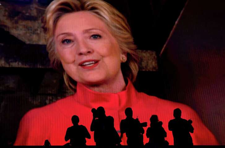 Silhouettes of photographers are seen as Hillary Clinton speaks via satellite Tuesday during the Democratic National Convention in Philadelphia.