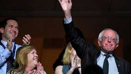 Former Democratic presidential candidate, Sen. Bernie Sanders, I-Vt., right, waves as he acknowledges applause during the second day of the Democratic National Convention in Philadelphia , Tuesday, July 26, 2016. (AP Photo/Mark J. Terrill)