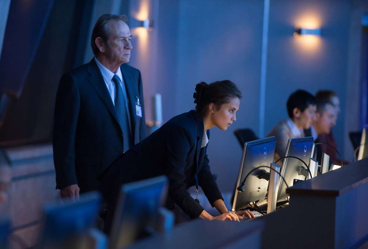 In this image released by Universal Pictures, Tommy Lee Jones, left, and Alicia Vikander appear in a scene from