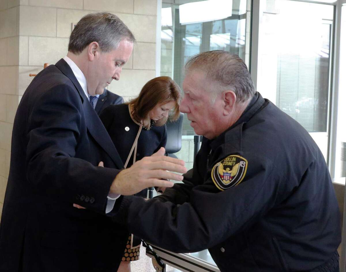 Texas Attorney General Ken Paxton and his wife Angela go through security as Collin County of Homeland Security officer John Elfers, right, checks Paxton at the Collin County Courthouse to hear pre-trial motions on charges of securities fraud on Tuesday, December 1, 2015. (David Woo/The Dallas Morning News)
