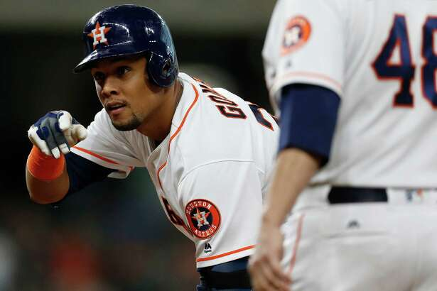 Houston Astros center fielder Carlos Gomez (30) points at the dugout after he singled during the second inning of an MLB game at Minute Maid Park, Wednesday, July 27, 2016, in Houston.