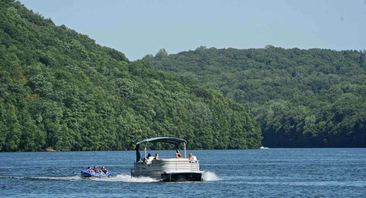 Ceci Schimenti, Michael Schimenti and Astrid Shay ride in a 3-person tube while being pulled by their grandparents boat on Lake Lillinonah on July 27, 2016.