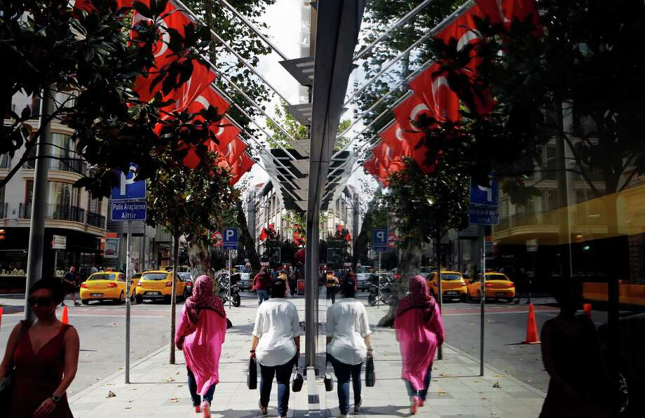 Women are reflected in a shop window as they walk at a shopping street in Istanbul, Wednesday, July 27, 2016. Turkey was riding high in 2010, casting its brand of Islamic piety, Western-style democracy and economic growth as a regional model amid popular upheavals in the Mideast and North Africa. ??Six years later, it is mired in tension with neighbors and allies, dominated by a president seeking to increase his constitutional powers and now enmeshed in a purge of large sectors of society after an uprising by renegade military officers (AP Photo/Petros Karadjias) ORG XMIT: XPK102 Photo: Petros Karadjias / Copyright 2016 The Associated Press. All rights reserved. This m