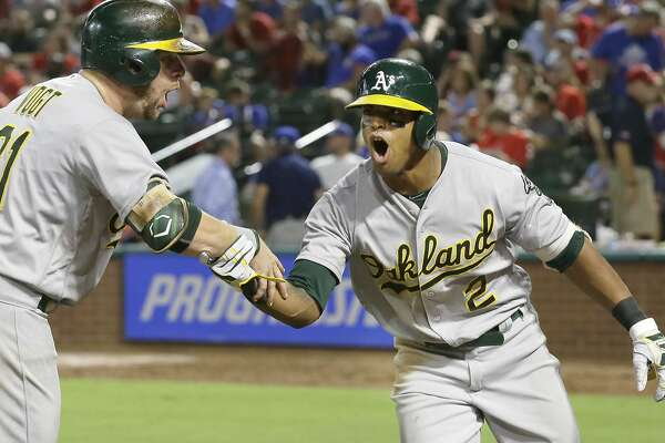 Oakland Athletics Khris Davis (2) celebrates his two-run home run with Stephen Vogt during the eighth inning of a baseball game against the Texas Rangers in Arlington, Texas, Wednesday, July 27, 2016. (AP Photo/LM Otero)