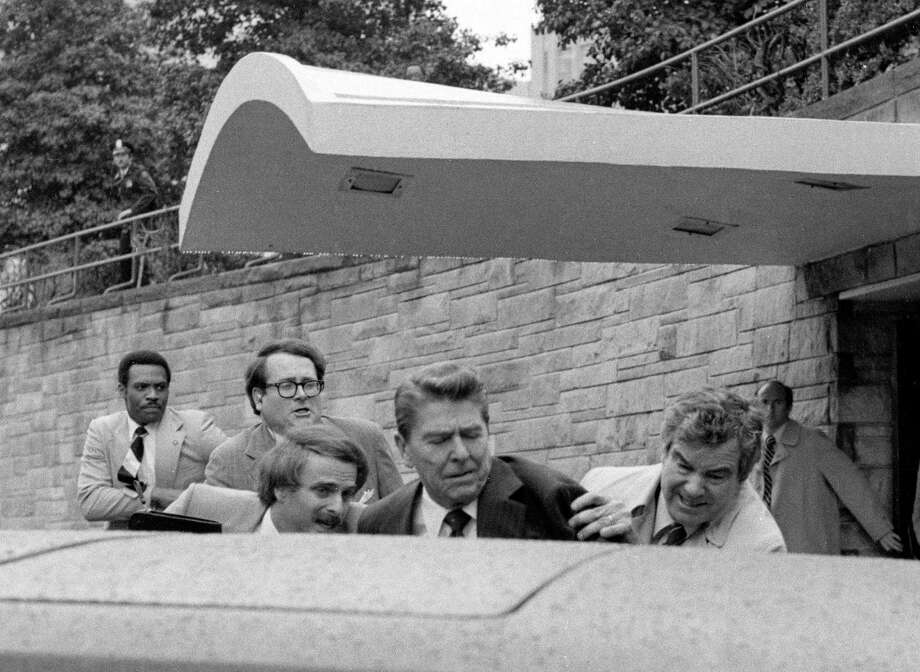 **FILE** U.S. President Ronald Reagan is shoved into the President's limousine by Secret Service agents after being shot outside a Washington hotel in this March 30, 1981, file photo. Reagan, the cheerful crusader who devoted his presidency to winning the Cold War, trying to scale back government and making people believe it was ''morning again in America,'' died Saturday, June 5, 2004, after a long twilight struggle with Alzheimer's disease. He was 93. (AP Photo/Ron Edmonds, File) Photo: RON EDMONDS / AP