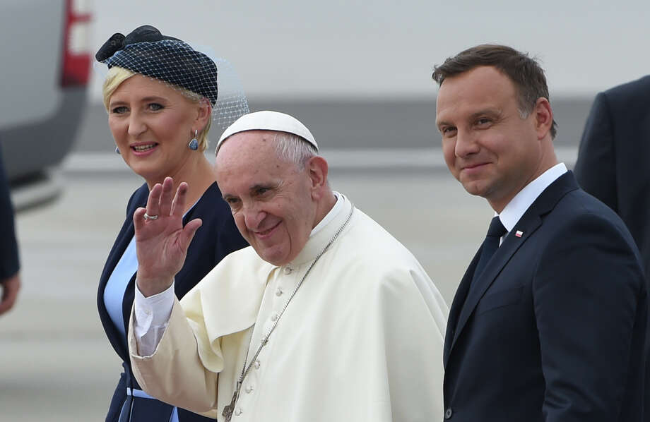 Pope Francis, center, greets faithful as he walks with Polish President Andrzej Duda, right, and his wife Lady Agata Kornhauser-Duda after arrival at the military airport in Krakow, Poland, Wednesday, July 27, 2016. (AP Photo/Alik Keplicz) ORG XMIT: XAK156 Photo: Alik Keplicz / Copyright 2016 The Associated Press. All rights reserved. This m
