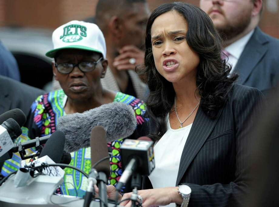 Baltimore State's Attorney Marilyn Mosby, right, holds a news conference near the site where Freddie Gray was arrested after her office dropped the remaining charges against three Baltimore police officers awaiting trial in Gray's death, in Baltimore, Wednesday, July 27, 2016. The decision by prosecutors comes after a judge had already acquitted three of the six officers charged in the case. At left is Gray's father, Richard Shipley. (AP Photo/Steve Ruark) ORG XMIT: MDSR109 Photo: Steve Ruark / FR96543 AP