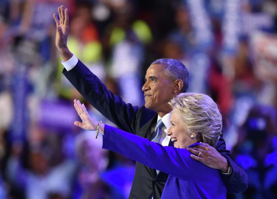 US President Barack Obama (L) waves with US Presidential nominee Hillary Clinton during the third night of the Democratic National Convention at the Wells Fargo Center in Philadelphia, Pennsylvania, July 27, 2016. / AFP / Nicholas Kamm        (Photo credit should read NICHOLAS KAMM/AFP/Getty Images) Photo: NICHOLAS KAMM/AFP/Getty Images