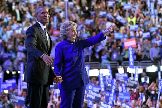 President Barack Obama stands with Democratic presidential candidate Hillary Clinton following Obama's speech at the Democratic National Convention from the Wells Fargo Center in Philadelphia, Wednesday, July 27, 2016.