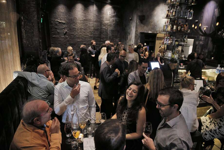 Guests enjoy food and drinks at the main bar at the new Black Cat. Photo: Carlos Avila Gonzalez, The Chronicle