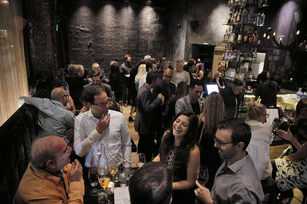 Guests enjoy food and drinks at the main bar at the new Black Cat Restaurant and Bar in San Francisco, Calif., on Wednesday, July 27, 2016. Black Cat opens Thursday, July 28, and features a jazz revue in the lower floor.