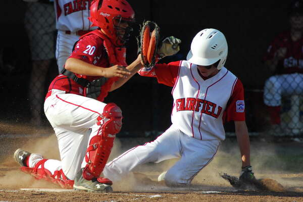 Fairfield American's Ben Gaffney slides safely into home during State Tournament action against Berlin on Wednesday at Dettore Field in Manchester. Fairfield American won 20-7.