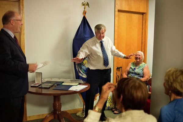 BRITTNEY LOHMILLER | blohmiller@mdn.net Retired Army Sergeant Ronald Hnizda tells a story about his time in basic training to Congressman John Moolenaar and family members during a presentation of military service awards on Wednesday afternoon.