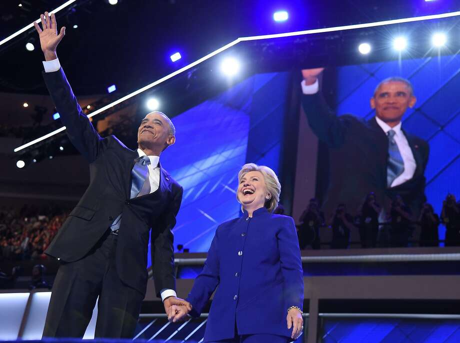President Barack Obama waves with nominee Hillary Clinton during the third night of the Democratic National Convention at the Wells Fargo Center in Philadelphia. Photo: ROBYN BECK, AFP/Getty Images