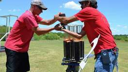 Setting up a trap machine that will throw targets similar to a going-away dove, Tommy Honey (left) and Richard Guilford of the San Antonio Gun Club help get the facility ready for its annual Hunter's League.